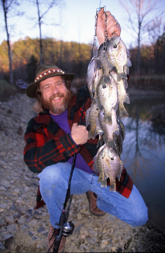 Bluegill angler with stringer of fish caught in fall, private lake in Saline County, Arkansas