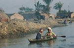 Marsh Arabs. Southern Iraq. Circa 1985. Marsh Arab men in boat banks of river Tigris.