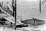 Photograph of the damage in Eastpoint after Hurricane Elena churned in the Gulf of Mexico off the coast of the Florida panhandle in September 2, 1985.  Elena was the first major hurricane of the 1985 season and it's unusual path included a loop and went back and fourth along the Florida panhandle as a category 3 storm heavily damaging the Apalachicola, FL oyster industry.  Apalachicola recorded the highest surge and rainfall totals and whatever oyster industry wasn't ruined by Elena was finished off when Hurricane Kate followed  in November of the same season.