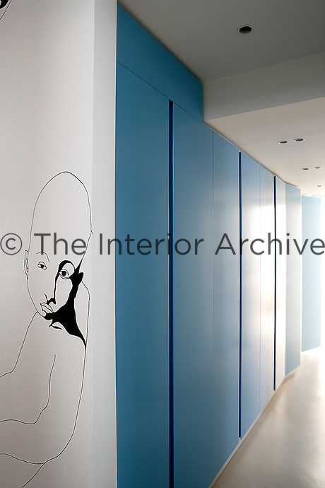 """The bedrooms, which all open on to an inner courtyard, run along this corridor behind panels painted a """"glacier blue"""""""