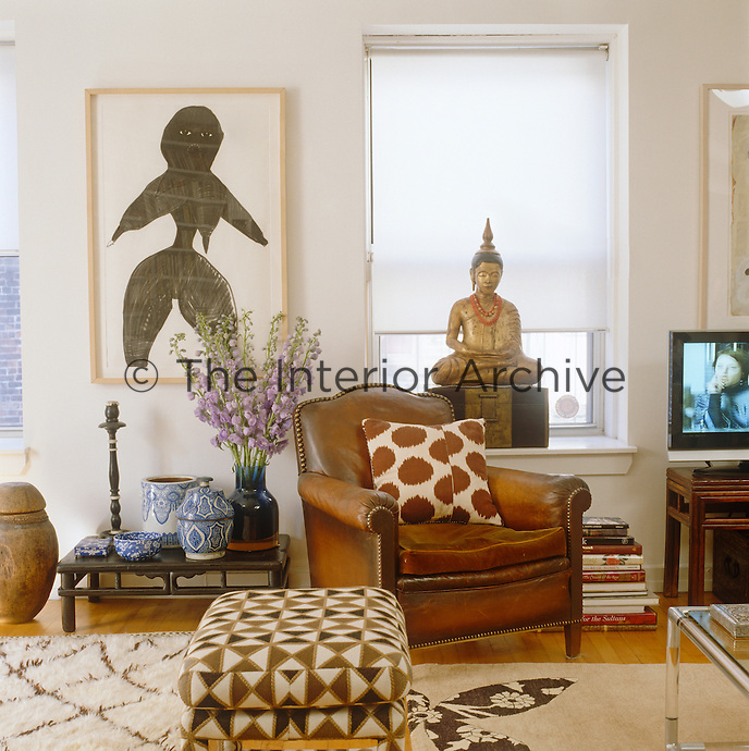 A corner of the apartment showing one of Madeline Weinrib's paintings, a leather armchair and a collection of blue and white china