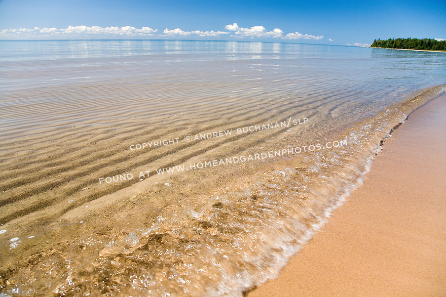 Ripples in the underwater sand as a small waves breaks along the shoreline of Lake Huron, in the eastern Upper Peninsula of Michigan with a blue summer sky and puffy white clouds above the distant curving horizon.