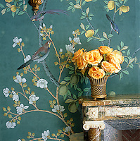 In the living room of a house designed by Charlotte Moss a bouquet of yellow roses in an antique latticework vase arranged on top of a carved marble fireplace