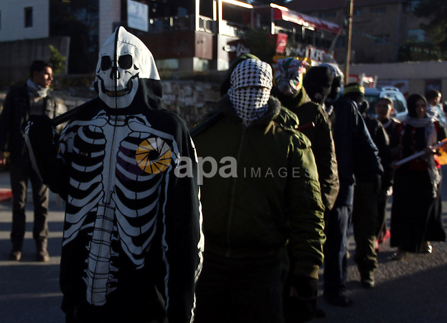 Palestinian supporters of Fatah movement wear military clothes as they march during a rally on the eve of the 48th anniversary of the formation on the Fatah movement, on December 31, 2012, in the West Bank city of Ramallah. The Fatah anniversary commemorates the first operation against Israel claimed by its armed wing then known as Al-Assifa (The Thunderstorm in Arabic) on January 1, 1965. Photo by Issam Rimawi