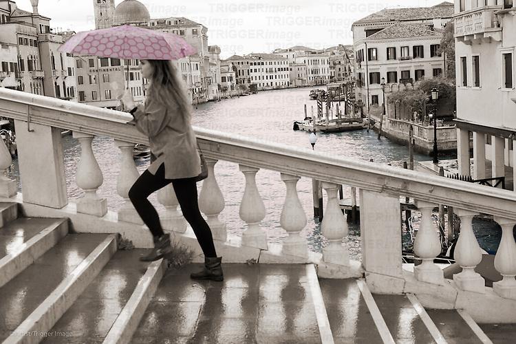 A female figure walks over a large bridge in Venice holding an umbrella