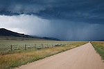 Storm clouds bringing summer rain and a rural gravel road near Dillon, Montana