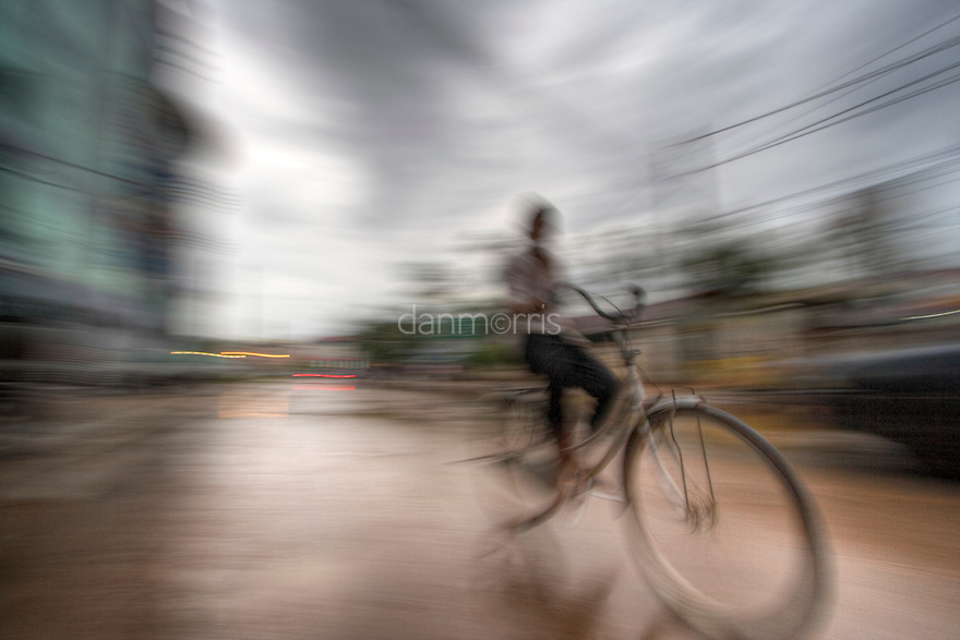 Boy rides bicycle through rainy streets of Siem Riep, Cambodia