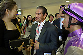 Renowned trainer Tony Cruz talks with a guest at the Hong Kong Jockey Club's Happy Valley racecourse. On the right is jockey Matthew Chadwick.