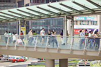 Hong Kong pedestrians crossing Connaught Road Central via footbridge towards Exchange Square