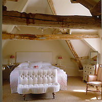 This cosy attic bedroom is criss-crossed with huge ancient roof beams