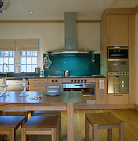 A stainless steel extractor hangs above a large granite spalshback in this blonde wood kitchen