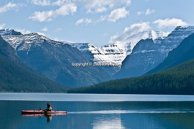 Kayaker boating and fishing on bowman lake tony bynum for Fishing in glacier national park