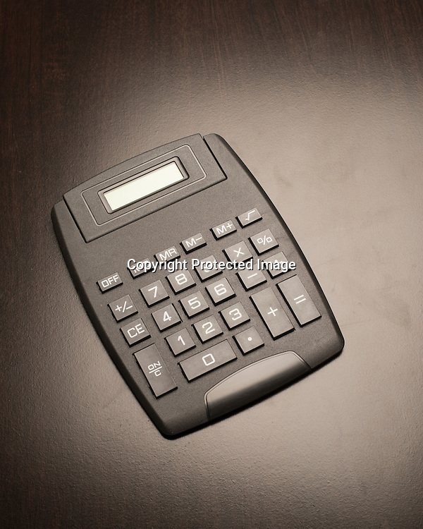 Black plastic calculator on a  wooden surface.