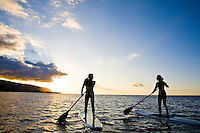 Young women standup paddling (SUP) at sunset off the shores of Mokuleia