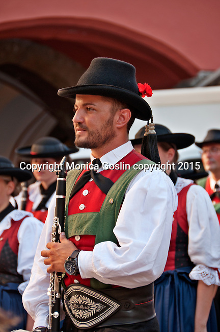 A local brass band, wearing traditional dress, plays on the plaza with the Golden Roof building; there are over 300 brass bands in Tyrol and open-air concerts are held year round and have been for over 200 years