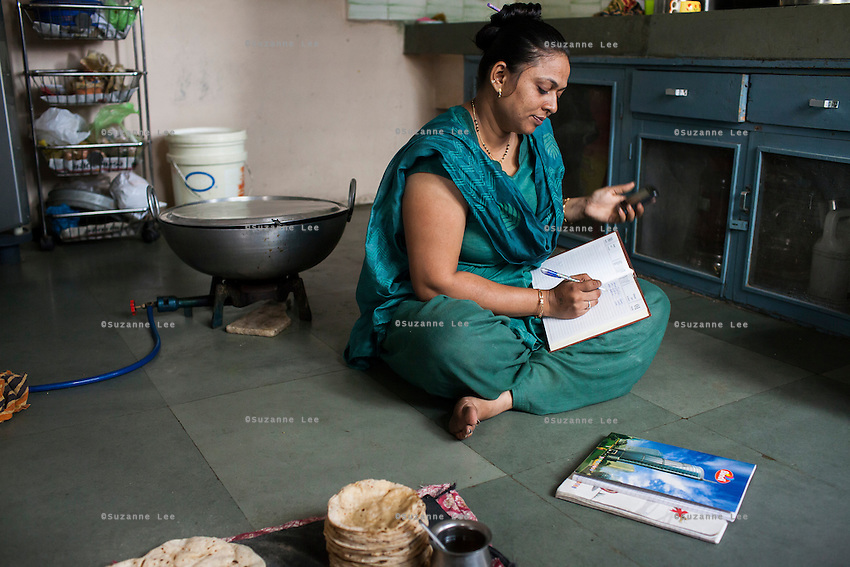 Archana, an ex-surrogate, looks into her accounts, as she continues to work with Dr. Nayana Patel catering specially prepared tiffin meals to the surrogates and Akanksha IVF and Surrogacy clinic staff, which she prepares in her house with her family in Anand, Gujarat, India on 11th December 2012. Photo by Suzanne Lee / Marie-Claire France