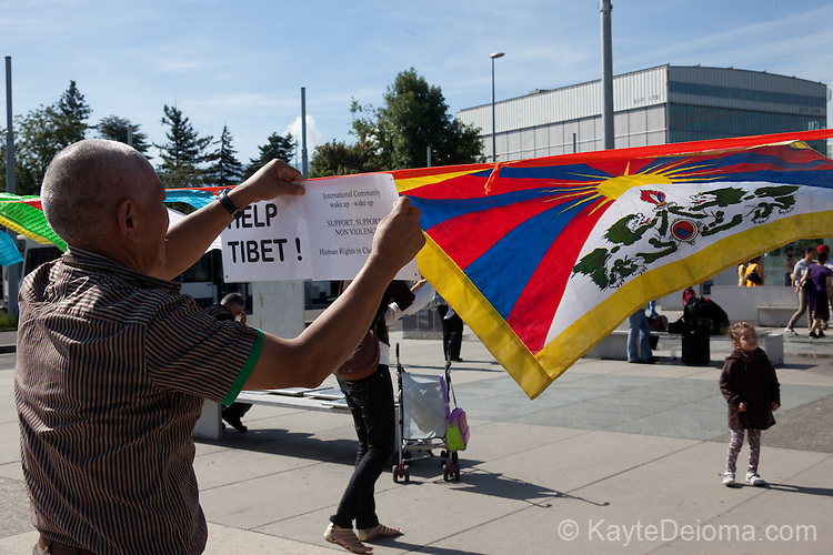 A man hangs Tibetan prayer flags in support of Human Rights in Tibet and China on the Place des Nations in Geneva, Switzerland