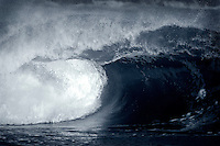 20 June 2006:  Single set wave rolls a shore during a South swell reaches the famous surf spot in Newport Beach, CA called The Wedge.  Surfers, boogie boarders, body surfers and crowds gather to watch the powerful waves and the waters take shape into unique sets along the jetty in Orange County, California.  Tube blue color conversion.