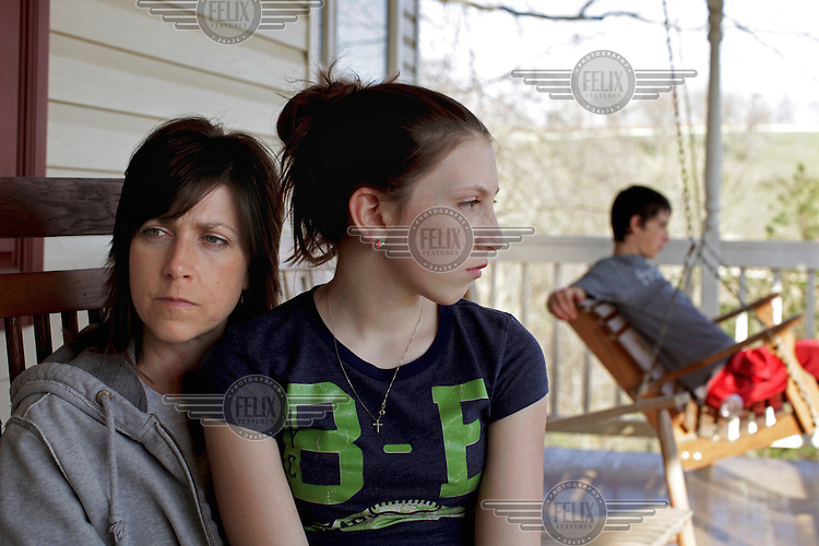 Stacey Haney sits with her 11 year old daughter Paige and 14 year old son Harley. Haney leased her land for shale gas extraction last year and problems have arisen ever since. First, local roads were destroyed. She and her family became ill and animals started dying – two dogs, a horse and the children's goat. She began to suspect their water and the fumes from the nearby chemical waste pond and compressors were poisoning them. Her son edged toward liver failure. After tests, their blood showed high levels of toxic chemicals including arsenic, toluene and benzene.