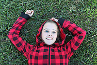 A young girl lies in the grass.