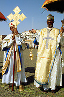 Eritrea. Asmara. September square. Meskel is the most important religious feast for the orthodox church in Eritrea. It takes place every year on september 27. A group of priests  dressed in white tunicle with holy crosses stand near the woodshed which will later be burnt.  Once fully burned, the crowd will run to the furnace, collect some unburn wood parts and pick up ashes to draw a holy black cross on their foreheads. A young priest holds a holy cross embroided with gold with Jesus.  © 2002 Didier Ruef