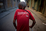 portrait of cuban elderly man on walker wearing fidel castro shirt