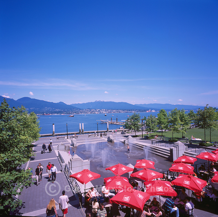 """People dining at the Mill Marine Bistro - an Outdoor Restaurant Cafe with Red Sun Umbrellas, and Children playing at Water Park, along Waterfront at """"Coal Harbour"""", in the """"West End"""" of Vancouver, British Columbia, Canada, in Summer.  The North Shore Mountains (Coast Mountains) rise in the background."""