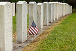 Head stones at cemetery on a Spring afternoon with grave stones in rows with American flag placed at one of the headstones Evergreen Washelli cemetery Seattle Washington State USA