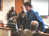 Sniper victim Jeffery Hopper, right, leaves court after his testimony during the trial of sniper suspect John Allen Muhammad, seated left, in courtroom 10 at the Virginia Beach Circuit Court in Virginia Beach, Virginia on October 30, 2003.  Hopper was shot in Ashland, Virginia, on October 19, 2002 and underwent 5 operations as a result of his wounds. <br /> Credit: Adrin Snider - Pool via CNP
