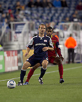 New England Revolution forward Ilija Stolica (9) passes as Real Salt Lake defender Rauwshan McKenzie (30) defends. In a Major League Soccer (MLS) match, Real Salt Lake defeated the New England Revolution, 2-0, at Gillette Stadium on April 9, 2011.