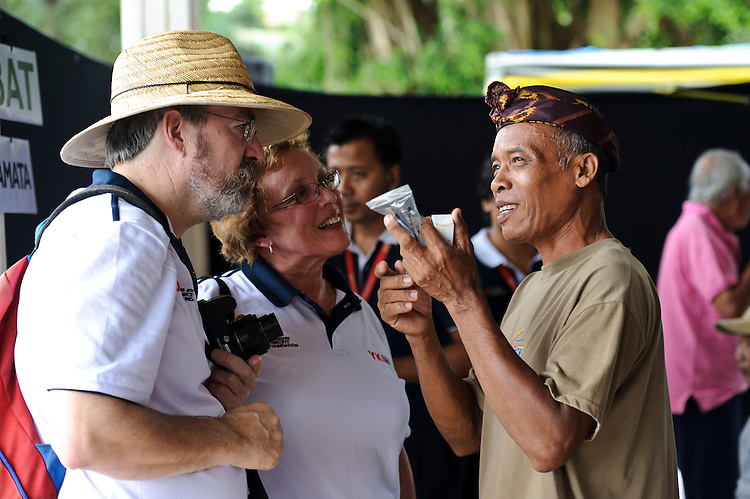 A man discussing his new corrective glasses with visitors to a mobile clinic, Bali, Indonesia.