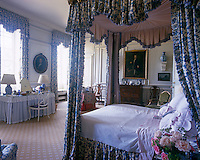This elegant bedroom is furnished with a four poster bed draped in a blue and white chintz with matching curtains