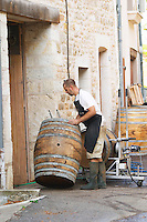 Oak barrel aging and fermentation cellar. Cleaning old barrels. The village. Pommard, Cote de Beaune, d'Or, Burgundy, France