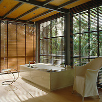 Timber blinds filter the light in the tranquil glass-walled bathroom