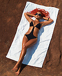 Beautiful suntanned woman lying on a beach towel on dry red soil
