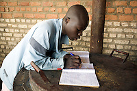 Rwanda. Southern province. District of Muhanga. Central jail of Gitarama. A black teenager boy reads his exercice book (homework book) on the huge metal pans of the kitchen. Bricks wall. Minors block. Minors in detention. Detention pending trial and after trial, sentenced to prison. The non-governmental organization (NGO) Fondation DiDé - Dignité en détention runs the Encademi (Encadrement des mineurs) program. Prison centrale de Gitarama. Quartier des mineurs.  © 2007 Didier Ruef