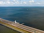 Nederland, Noord-Holland, Gemeente Wieringen, 16-04-2012; Afsluitdijk ter hoogte van het Monument, de plaats waar in 1932 De Vlieter, het laatste gat, werd gesloten. De 32 kilometer lange dijk vormt de waterkering tussen Waddenzee (links) en IJsselmeer (rechts), aan de horizon is de kust van Friesland zichtbaar. Aanleg van de dijk vormde onderdeel Zuiderzeewerken, initiatief van ingenieur Cornelis Lely..Enclosure Dam at the height of the Monument, where in 1932 the Vlieter, the last opening, was closed. Frisian coast at the horizon (32 kilometers away).The dike forms the barrier between the Wadden Sea (left) and IJsselmeer lake (right), Frisian coast at the horizon (32 kilometers away)..luchtfoto (toeslag), aerial photo (additional fee required)..foto/photo Siebe Swart