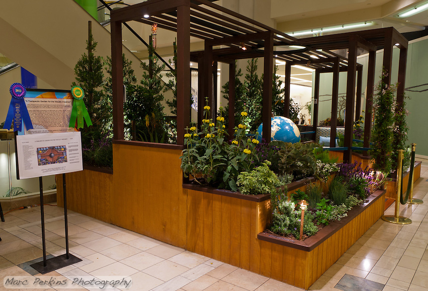 """A 3/4 view (with award ribbon visible!) of Orange Coast College's Ornamental Horticulture Club's first-place winning garden installation at the 2012 South Coast Plaza Spring Garden Show in Costa Mesa, CA.  The theme for the show was """"healing gardens"""", and the OCC team installed a """"garden for the visually impaired.""""  The garden's centerpiece is a 1957 restored globe for the blind, with the world geography in exaggerated height to be sensed by the touch of blind people; the locations of plants in the garden was indicated in braille on the globe.  This picture was taken Thursday April 27, 2012 at ~9pm, less than 48 hours after my in-progress pictures."""