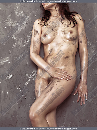 Beautiful young naked woman with shiny soiled body leaning against a rustic wall