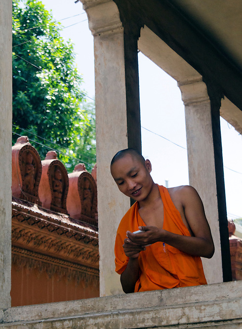 Buddhist monk in orange robe uses his cell phone
