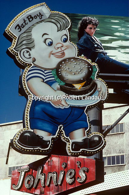Sign for Johnies Fat Boy restaurant and blue jean billboard at Wilshire and Fairfax in Los Angeles, CA