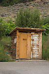Two-holer, two door, rough-cut wooden outhouse along the highway in British Columbia