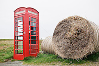 Traditional red telephone booth with bailes of hay, Isle of Skye, Scotland