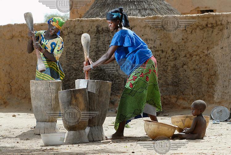 """Nana Badama (left) and Hinda Salha (right) grind millet to make an edible """"kalebash"""" paste in Dan Saga village."""