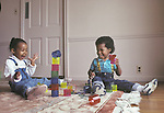 Oakland CA 2-yr-old boy/girl friends delightedly playing with building toy