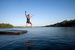 A mid thirties red head female airborne while jumping into a lake late on a summer afternoon.