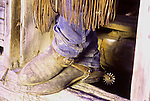 A cowboy's broken-in trusty old boots in the doorway of an old log cabin on a ranch in Western United States.