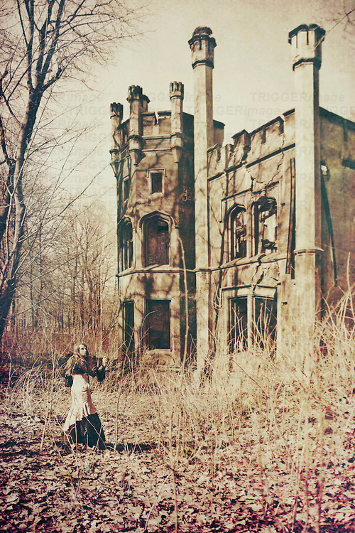 The girl in victorian gown with long hair in front of a large castle looking back