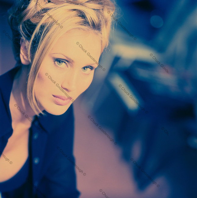Blue and pink toned cross process photo of a blond woman wearing black and looking at camera.