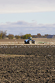 Large farm tractor discing field in fall